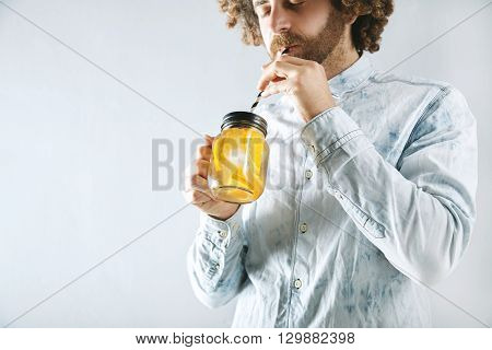 Young Bearded Man In Light Jeans Shirt Drinks Fresh Home Made Orange Citrus Sparkling Lemonade Throu