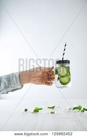 Bartender Hand Holds Fresh Cold Lemonade From Cucumber And Mint In Rustic Jar With Striped Straw Abo
