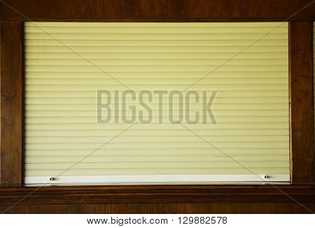 a brown shutters on the shop window