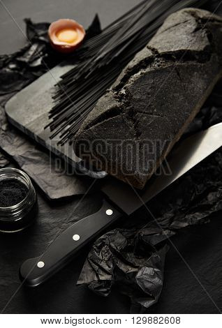Top View  Black Spaghetti On Stone Marble Desk With Black Bread; Caviar In Transparent Jar, Chief Kn