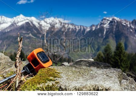 Action camera is resting against a rock with a mountain panorama as background