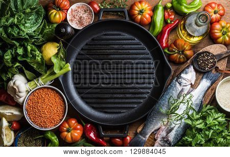 Ingredients for cooking healthy dinner. Raw uncooked seabass fish with vegetables, grains, herbs and spices over rustic wooden background, cast iron pan in center with copy space. Top view