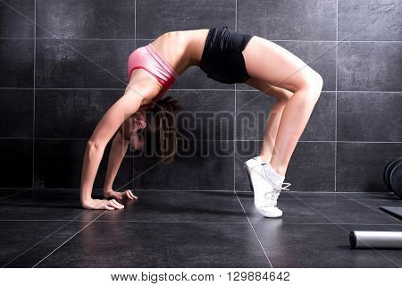 Young, beautiful woman doing exercises in the gym