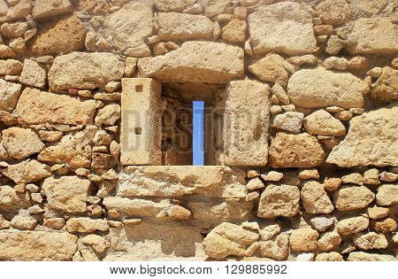 Window in old stone wall ruins of a medieval fortress on Crete Island, Greece