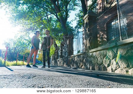 Young couple talking and chatting in the sunset in a urban environment.