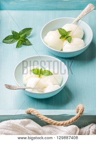 lemon sorbet ice cream with mint in bowls over turquoise blue background, selective focus
