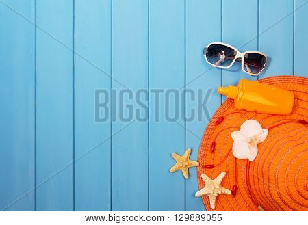 Hat, sunglasses and suntan lotion on wood background colored in blue.