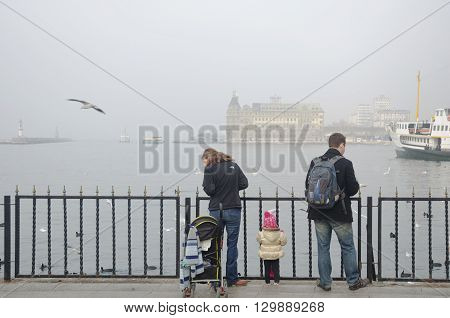 Istanbul Turkey - January 5 2014: Istanbul dense fog in the throat was found to affect the transportation and daily life. A family waiting for ferry travel when feeding seagulls were seen.
