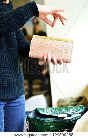 Woman saving money in wallet. Taking change. Fancy style.