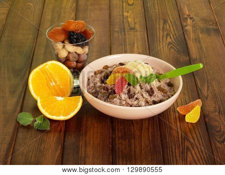 A cup of oatmeal, dried fruit, nuts and orange against the dark wood. Healthy eating.