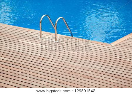 Blue swimming pool with teak wood floor stripes summer vacation