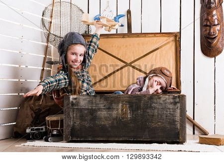 two playful little girls pretending pilots in old big wooden chest