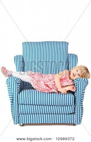 little girl wearing dress and shoes is lying on comfortable chair. isolated.