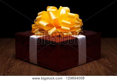one large red gift box with yellow bow on a wood background