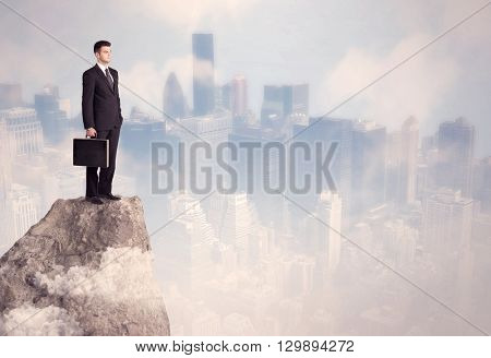 A successful good looking businessman standing on top of a high cliff above the city scape with clouds concept