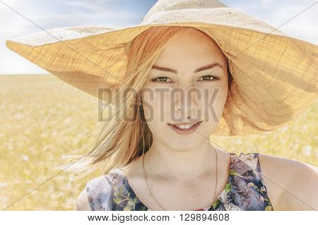 portrait of a girl with a hat in summer field. attractive blond woman in flower dress and wide-brimmed hat. close up. looking at the camera