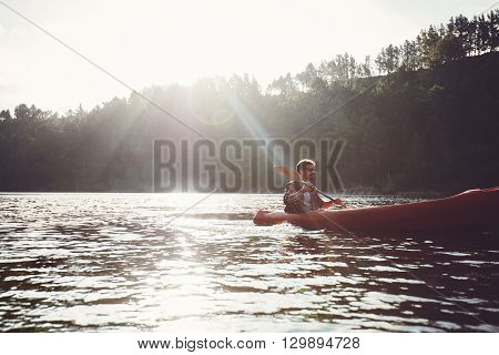 Young man canoeing in a lake. Man paddling kayak on a summer day.
