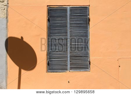Light orange wall with a window with a closed grey grid. Shadow of a round traffic sign of the window. Just a shadow of the rules?