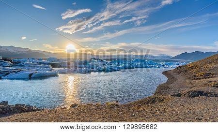 Beautiful view of icebergs in Jokulsarlon glacier lagoon at sunset Iceland; selective focus