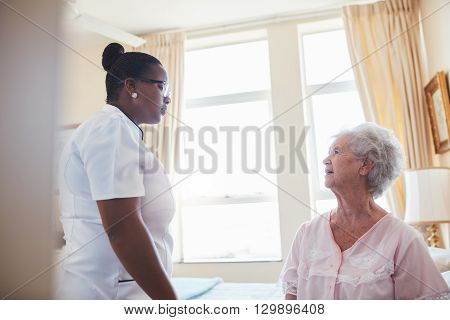 Indoor shot of female doctor visiting her senior patient for routine checkup at home. Nurse talking with old woman sitting on bed.