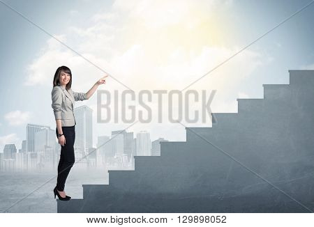 Businesswoman climbing up a concrete staircase concept on city background