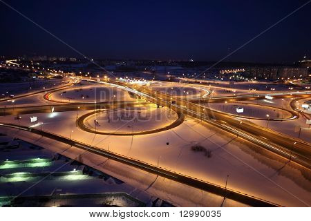 night winter cityscape with big interchange, lighting columns and garages, dark blue sky