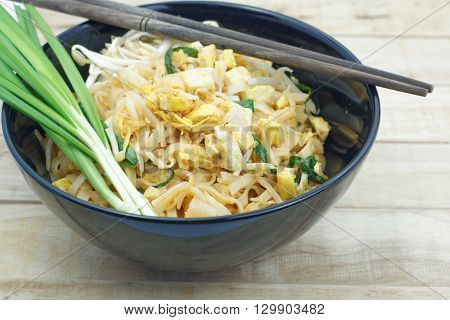 Thai fried noodle in black bowl with bean sprouts and Garlic chives on topping. Pad Thai in a black bowl put on wood table.