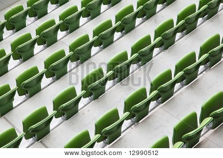 Many rows of green, plastic, folding seats in a big empty stadium.