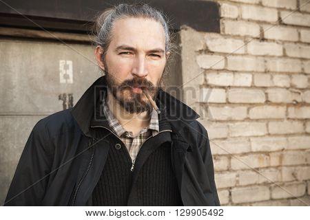 Bearded Man Smoking Cigar Over Old Brick Wall