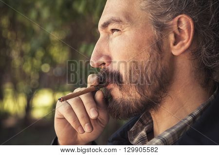 Bearded Asian Man Smoking Cigar, Outdoor