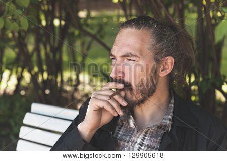 Bearded Asian Man Smoking Cigar In Park