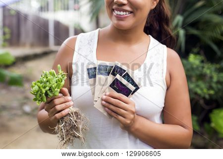 Woman holding packets of organic seeds against a wooden wall. (Written in Spanish: Coriander seeds, mustard seeds, arugula seeds and radish seeds)