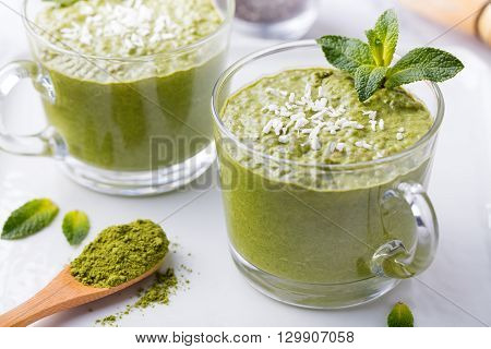 Matcha green tea chia seed pudding, dessert with fresh mint and coconut on a white stone background Healthy breakfast Copy space