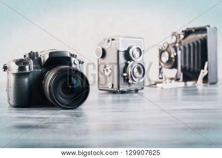 Three different camera on grey wooden desktop