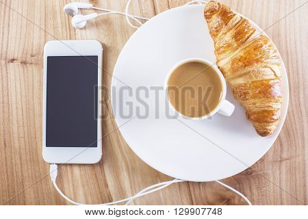 Topview of wooden desktop with blank smartphone coffee and croissant. Mock up