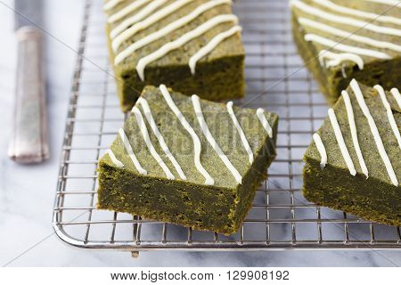 Matcha green tea brownie cake with white chocolate on a cooling rack. Grey stone background