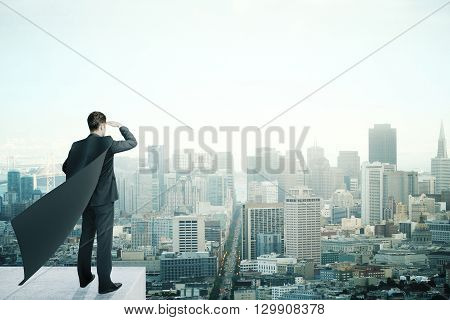 Businessman with black superhero cape standing on pedestal and looking into the distance on cityscape background