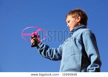 little boy in blue jacket plays with pink propeller. in background blue sky
