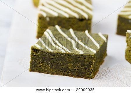 Matcha green tea brownie cake with white chocolate on a white plate Grey stone background