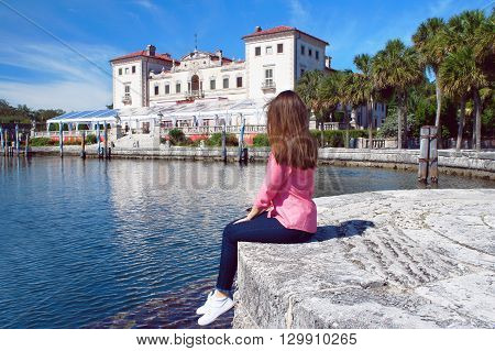 Tourist girl look at the Villa Vizcaya of Biscayne Bay in Miami.