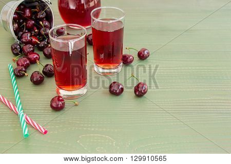 Left an inverted bucket of cherries, cherries scattered, 2 glasses of juice, jug of cherry juice, on right empty space for text on green background. Cherries, cherry juice and empty space. Horizontal.