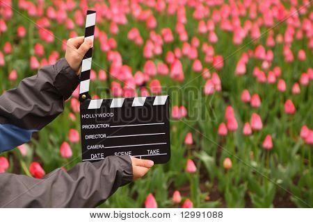 Junta de badajo de cine en manos de niño en campo con tulipanes