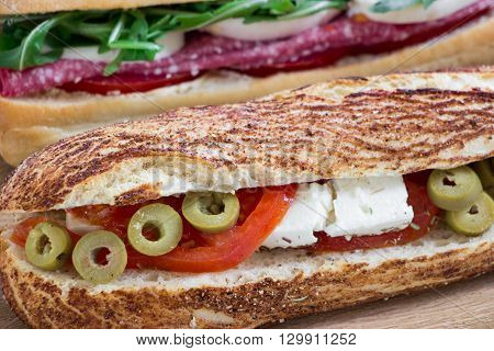 Diagonally in the foreground lying sandwich with feta cheese olives tomatoes and behind sandwich with salami mozzarella arugula tomatoes on the light wood background. Greek style sandwich. Horizontal. Daylight. Close.