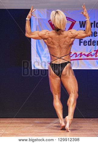 MAASTRICHT THE NETHERLANDS - OCTOBER 25 2015: Female fitness model Gerbel Mikk flexes her muscles and shows her best physique in a back double biceps pose on stage at the World Grandprix Bodybuilding and Fitness of the WBBF-WFF