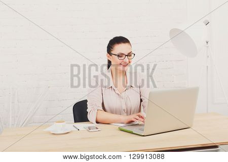 Middle aged businesswoman working in white modern office interior, with laptop. Female office work, woman in eye glasses, smiling. High key, soft tone. woman in office.