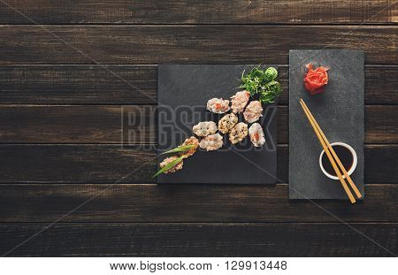 Japanese food restaurant, sushi gunkan roll plate, platter set. Creative food. Set with chopsticks, ginger, soy, wasabi. Sushi at rustic wood background and black stone. Flat lay, top view. Copyspace.