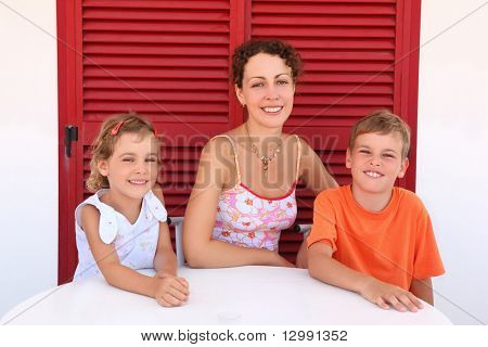 Mother with two children sit near shut  door to  round table and smile