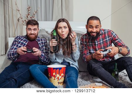 Three young friends playing computer games and drinking beer on the floor in living room