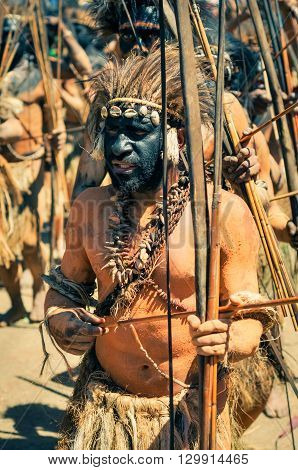 Wabag Papua New Guinea - August 2015: Native half-naked man with black colour on face holds arrow and bow and wears headband with feathers during traditional Enga cultural show in Wabag capital of Enga Province Papua New Guinea. Documentary editorial.