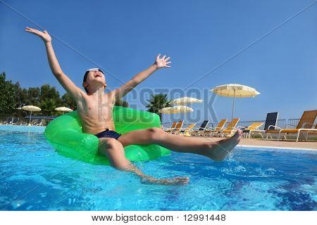 Boy sits on an inflatable arm-chair in  pool and with gladness lifts hands and head upwards in sky, underwater package shot